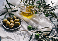 Branch of olives with a glass dish of olive oil (PrgomeljaDusanAna) Tags: wood food plant black green home cooking nature yellow horizontal fruit vintage table greek cuisine restaurant photo leaf vegan healthy spain italian mediterranean raw european branch bright eating background object border rustic cook olive tasty bowl vegetable fresh virgin spanish health homemade vegetarian oil taste growing concept setting aromatic extra aroma ingredient