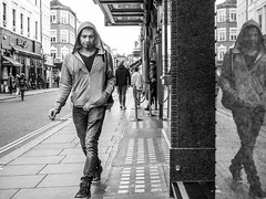 Stone faced reflection (Street matt) Tags: street blackandwhite bw man reflection london closeup walking candid streetphotography smoking hoody solitary streetmatt