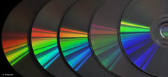 Spectrum 2 (Captivated by DVD's) (+Pattycake+) Tags: light music macro reflection closeup canon photo droplets rainbow shiny colours spectrum sparkle pattycake textures canonrebel cds simple plain minimalist lightmusic canoneos450d canonrebelxsi rainbowcd choccocupcake canonr450d