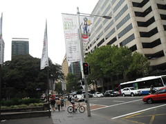 HOT AND OVERCAST (RubyGoes) Tags: city blue red sky white building bus cars buildings cyclist traffic pavement sydney australia nsw pedestrians banners therocks australiaday offices