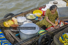 A sandwich on Mekong (Barbara Oggero) Tags: streetphotography travel indochina asia vietnam mekong river delta market hotdog food streetfood people boat water capture candid daylife