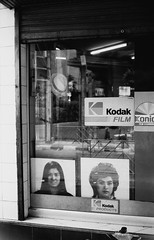 Kodak Products - Bangkok (35mm) (jcbkk1956) Tags: film window glass shop 35mm mono blackwhite photos kodak photographic retro konica manual thonglo ilfordpan100 konicaautos2 sukhumvitrd worldtrekker