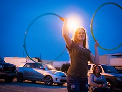(heatherbirdtx) Tags: blue sky music woman motion color girl composition evening dance eyecontact dusk streetlamp expression availablelight hula parking lot twirl flare jam hoops