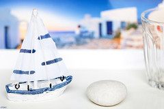 Good memories never fade.... (eleni m) Tags: memories greece stilllife white blue picture glass pebble boat indoor dof houses sky sea