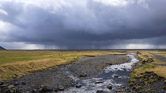with Spring comes the rain (lunaryuna) Tags: sky panorama water rain weather clouds season landscape iceland spring solitude path brook lunaryuna plain cloudscape vastness rainclouds mountainstream southiceland rainfront weathermood seasonalwonders