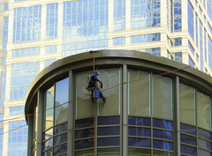 High in Chicago (Renee Rendler-Kaplan) Tags: city blue windows man male glass up work canon him bucket downtown sitting working may brush cleaning equipment sit there ropes he windowwasher seated dangling tethered suds wbez chicagoillinois employed sudsy chicagoist 2016 chicagoreader reneerendlerkaplan workenvironments canonpowershotsx530hs highinchicago