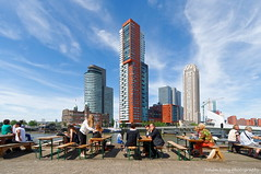 Lunch time at the skyline (Johan Konz) Tags: lunchtime people skyline kopvanzuid rotterdam netherlands outdoor cityscape cityview waterscape nieuwemaas rijnhaven hotelnewyork architecture building buildingcomplex blue sky nikon d90 city town harbour port
