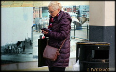 Tech-savvy granny (* RICHARD M) Tags: street winter senior sunglasses scarf liverpool portraits concentration candid character cellphone murals shades smartphone portraiture mobilephone february granny oblivious oap merseyside scouser litterbin shoulderbag streetportraits concentrating pensioner engrossed liverpudlian streetportraiture keepingwarm neckscarf winterclothing candidportraits candidportraiture sunspecs techsavvy quiltedcoat wellwrappedup bubblecoat
