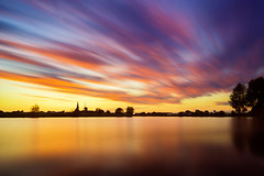 Stretching it (PhotoSolutions   pure photography) Tags: longexposure pink sunset sun nature water netherlands colors landscape colorful le beesd betuwe