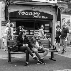 Tocco's (Howie Mudge LRPS) Tags: man men woman women people candid casual portrait photography bench pavement seat shop toccos blind walk walking sitting torquay devon england outside outdoors mono monochrome blackandwhite blackwhite bw street streetphotography urban urbanphotography sonyrx100iv compactcamera