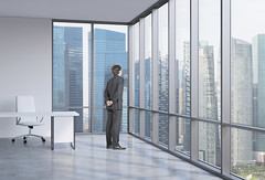 Young businessman is looking through the corner window. Singapore background. (designteambrussel) Tags: city inspiration window glass businessman architecture corner standing buildings asian corporate town office chair singapore downtown looking skyscrapers employment desk interior thoughtful competition professional business suit company planning thinking ceo imagination cbd concept innovation manager challenge leadership visionary contemplation career successful