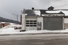 Motordrome (splorp) Tags: street door winter snow canada building abandoned wet monochrome grey exterior garage gray monochromatic alberta coleman vision:text=0653 vision:outdoor=0937