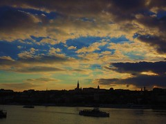 Budapest Sunset (valenzacalogero) Tags: city trip blue sunset shadow red sky sun reflection travelling wet water silhouette clouds buildings river crazy still cool europe poetry sailing ship nuvola time awesome budapest sightseeing cielo stunning romantic melancholy incredible acqua