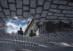 entering cloursphere (marianna - away for a while) Tags: old city blue sky people urban reflection water puddle hole montreal cobblestones cover manhole marianna armata