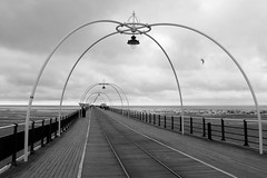 Southport Pier (togwood) Tags: sea sky blackandwhite bird architecture clouds fence mono seaside sand cloudy britain gull shapes picasa southport tramtracks leadinglines southportpier