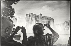Vegas Tourists enjoying the... Nah , Vegas Tourists framing the show. (steven -l-l-l- monteau) Tags: road camera trip las vegas blackandwhite bw usa west water analog america 35mm coast photo eau phone desert noiretblanc lasvegas kodak nevada trix jet streetphotography tourist nb strip 400 m42 shooting streetphoto flektogon steven bellagio 20mm framing fountains expired fontaine enjoying