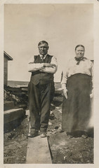 Grumpy couple poses outside (simpleinsomnia) Tags: old white black monochrome yard vintage found outside blackwhite couple arms antique fat snapshot dirt photograph elderly vernacular heavy grumpy crossed foundphotograph armscrossed