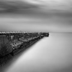 Seawall (Aleksandr Smirnov) Tags: longexposure sea blackandwhite bw seascape monochrome coast pier minimal minimalism breakwater waterscape
