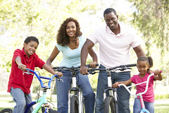 Young Family Riding Bikes In Park (The Daniel Plan) Tags: park family boy portrait people woman man male girl smile smiling bike bicycle horizontal female children outside outdoors happy person cycling countryside thirties healthy dad cyclist child father helmet daughter fulllength mother mountainbike son riding mum parent together cycle africanamerican bikeride enjoying fit 30s active fiveyearold havingfun fourpeople 8yearold cycleride 5yearold eightyearold safetyhelmet atcamera