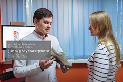 Woman consulting foot doctor (creativemarket.photo) Tags: show woman man promotion horizontal computer advertising foot shoe model technology cabinet tell room talk scan monitor patient medical health doctor footwear advert medicine advice benefit explain advantage orthopedics effective promote orthopedy orthopedist orthopaedics orthopaedist orthopaedy