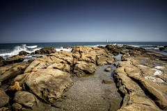View from the Rocks (MDM-photography) Tags: ocean longexposure travel sea holiday beach weather spain sand rocks warm europe waves rocky windsurfing splash vignetting