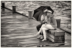 Students #2 (Claus Tom) Tags: street blackandwhite bw woman man male students hat rain weather female port umbrella copenhagen denmark harbor clothing student marine couple eyecontact candid border streetphotography rainy transportation accessories cph cloths toned climate kbenhavn accessory toning islandsbrygge attire