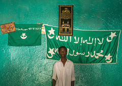 Sufi young man worshipper in front of islamic flags, Harari region, Harar, Ethiopia (Eric Lafforgue) Tags: africa travel portrait people man color green horizontal outdoors photography day adult african flag muslim islam faith religion indoor unescoworldheritagesite unesco indoors spirituality ethiopia sufi sufism worshipper mecca oneperson kaba hornofafrica ethiopian harrar eastafrica placeofworship kaaba harar abyssinia arabiccalligraphy traditionalclothing lookingatcamera meccah harari oromo onemanonly waistup 1people harer harariregion hararjugol harergeprovince harergey ethio162910