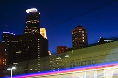 The Departure (FiddleHiker) Tags: longexposure blue light motion minnesota yellow train twilight cityscape skyscrapers minneapolis twincities lightrail lrt nightphotos metrotransit sonynex5n vivitar28210mmf3556forminoltamd