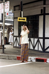 19-450 (ndpa / s. lundeen, archivist) Tags: street city people woman color film 35mm thailand bangkok sandals nick citylife streetlife pedestrian skirt nun sidewalk thai 1970s crosswalk 1972 curb 19 youngwoman 1973 dewolf nickdewolf photographbynickdewolf sivadol reel19 sivadolbuilding