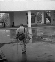 Ricoh TLS 401 with Helios 44-2 - Man Walking in Rainy Day (Kojotisko) Tags: street city people bw streets person czech streetphotography brno cc creativecommons czechrepublic streetphoto persons ricoh helios442 ricohtls401 helios442258 ricohtls