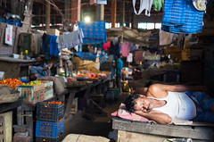 Snoozing in New Market (phil.w) Tags: street new old travel sleeping india man fruit living nap tank pentax market top ss streetphotography stall clothes snooze vegtables hanging inside clothesline undershirt limited kolkata hogg smcpfa31mmf18