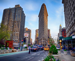 Flatiron Building in New York City (` Toshio ') Tags: toshio manhattan newyork newyorkcity flatironbuilding flatiron midtown city building architecture street taxi cab corner fujixe2 xe2 traffic clock man pedestrian apartments perspective