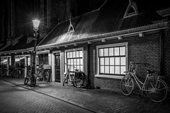 Overnight parking (McQuaide Photography) Tags: haarlem noordholland northholland netherlands nederland holland dutch europe sony a7rii ilce7rm2 alpha mirrorless 1635mm sonyzeiss zeiss variotessar fullframe mcquaidephotography lightroom adobe photoshop tripod manfrotto light licht night nacht nightphotography stad city urban lowlight architecture outdoor outside illuminated street straat oudegroenmarkt window wideangle wideanglelens groothoek building longexposure blackandwhite blackwhite bw mono monochrome atmosphere cobblestone cobbledstreet oldstreet old oud character traditional authentic streetlight lantaarnpaal bike bicycle fiets parked parking