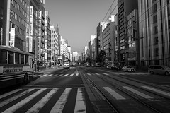 Leading Lines in Hiroshima (Aymeric Gouin) Tags: voyage road street city travel light shadow white black building cars monochrome car japan architecture asia cityscape shadows noiretblanc olympus hiroshima route asie crosswalk rue rues japon ville omd batiment honshu em10 chugoku aymgo aymericgouin