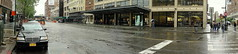 Panoramic View Of Apple Store and Other Retailers At 9th Avenue and 14th Street Manhattan (nrhodesphotos(the_eye_of_the_moment)) Tags: trees windows people urban signs cars glass rain metal architecture reflections advertising droplets chelsea shadows outdoor streetlights candid streetscene applestore panoramic cobblestone sidewalk vehicles transportation billboards westside 14thstreet autos westsidehighway awnings plantlife umbellas builidngs dsc00746 meatmarketdistrict wwwflickrcomphotostheeyeofthemoment theeyeofthemoment21gmailcom