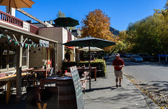 Deciding on the Best Place for Dinner (Jocey K) Tags: street autumn trees newzealand sky people signs architecture umbrella buildings pub shadows chairs autumncolours tables shops southisland centralotago cafes arrowtown tripdownsouth