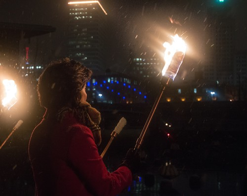 Governor Gina Raimodo holds a torch during the WaterFire Lighting Ceremony. Photo by Jen Bonin.