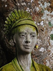 the snail ear pendant (SM Tham) Tags: bali tree statue lady indonesia outdoors island asia snail watergardens trunk lichen waterpalace karangasem tirtagangga amlapura