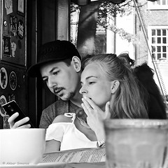TWO SOULES ONE PHONE (Akbar Simonse) Tags: dscn3153 sgravenhage haag lahaye thehague holland netherlands nederland streetphotography straatfotografie people candid man woman phone smartphone mobilephone zwartwit bw blancoynegro bn monochrome vierkant square akbarsimonse