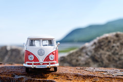 VW by mountains and by sea (le cabri) Tags: van sixties 60s 60s volkswagen volks red toy bus mountain sea iconic transportation landvehicle water bluesky bokeh sunlight outdoors germanculture german germany hippie cute toycar retro retrostyled replica 19601969 1960 frontview europe old fashion katabatik