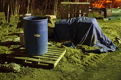 Barrel, Tarp, and Pallets (Pythaglio) Tags: wood autumn trees leaves metal construction long exposure michigan debris barrel tracks plastic equipment dirt pallets hillsdale tarp 20second