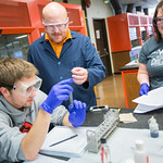 A professor conversing with two of his students as they complete a lab.