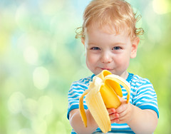 happy kid eating banana fruit. healthy food eating concept. (TrimDownClub) Tags: boy food baby cute male beautiful yellow fruit studio lunch one kid healthy toddler funny pretty child natural emotion bokeh outdoor background small adorable blurred banana vegetarian cheerful additional nutrition caucasian curlyheaded
