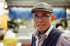 Friendly oji-san (Eric Flexyourhead (shoulder injury, slow)) Tags: man japan zeiss japanese tokyo bokeh   kitaku shallowdepthoffield shopkeeper kajiwara ojisan    55mmf18 sonyalphaa7 zeisssonnartfe55mmf18za