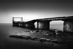 Abandoned pier (ilias varelas) Tags: longexposure light sea blackandwhite bw seascape water monochrome canon mono pier rocks mood cloudy ilias canonef1740mmf4l varelas canoneos6d