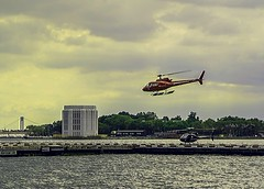 Coming In For Landing To Helipad At East River NYC (nrhodesphotos(the_eye_of_the_moment)) Tags: dsc0640372 theeyeofthemoment21gmailcom wwwflickrcomphotostheeyeofthemoment helicopter helipad landing architecture outdoor season metal glass sightseeing tourists governorsisland eastriver waterfront verrazanobridge skyline buildings trees plantlife plants water sky clouds batterytunnelexhaust span reflections shadows nyc manhattan downtownmanhattan transportation