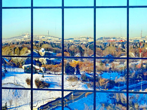 blue trees windows red orange white snow canada black cold green calgary sunshine yellow buildings reflections grey shadows distorted warped hills alberta valley highways wobbly glassbuildings 25faves peggyhr frameit~level01~ visionaryartsgalleryl1