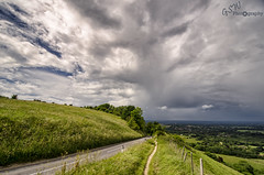 Sunshine to the left of me, clouds to the right, here I am (Gavmonster) Tags: road uk blue trees sky white storm green rain weather clouds landscape grey sussex nikon unitedkingdom path fluffy wideangle fields thunderstorm lightning eastsussex thunder stormchasing ditchlingbeacon stormchaser stuckinthemiddle ukstorm 1024mm d7000 nikond7000 gswphotography