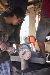 Two men stand on the form barefoot, while the other man pours molten aluminum.