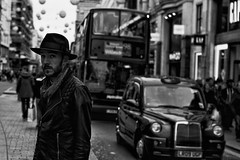 IMG_8519-Edit (roger_thelwell) Tags: life street city uk winter portrait england people urban bw white black streets cold london lamp monochrome westminster beauty hat rain leather mobile umbrella hair bag walking real photography mono chat shiny phone traffic post natural photos britain circus cigarette candid cab taxi great over sac hats cell photographic smoking lamppost photographs oxford conversation shiney talking shoulder handbag stud speak speaking studs commuters scak